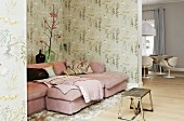 Pink couch and retro wallpaper in living area; vintage table in foreground
