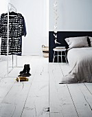 Simple, minimalist bedroom with white wooden floor and black and white dress on clothes rack