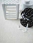 Shabby chic stool with woven seat and polka-dot hat box on white carpet