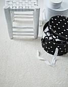 Flechthocker im Shabby Stil und Hutschachtel mit Pünktchenmuster auf weißem Teppichboden