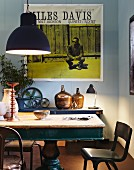 Vintage table and chairs illuminated by large pendant lamp; Miles Davis poster on wall