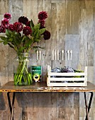Splendid bouquet of dahlias in glass vase on vintage table against concrete wall with collage of wooden cutlery