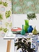 Collection of vases in shades of green and blue arranged on runner in front of various samples of floral wallpaper