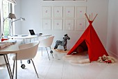Two workstations with modern shell chairs at desks on castors and toys around red teepee in corner of room