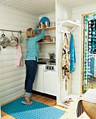 Woman in small kitchen of Swedish holiday home