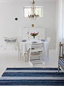 Swedish-style dining room in white & blue with set table & chandelier
