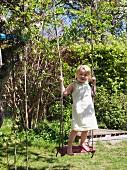Little girl standing on swing in garden