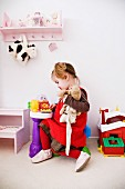 Little girl playing in child's bedroom