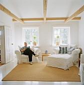 Mann sitting reading in white armchair