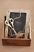 Slate, scissors and string in wooden drawer
