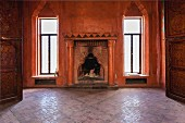 View through open door of fireplace with columns and walls painted rust red