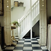 Snow-white, country-house staircase, traditional, chequered tiled floor and folding doors with peeling paint