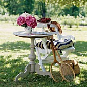 Cherries and hydrangeas on round wooden table and tennis racquets leaning on chair in sunny garden