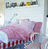 Various red gingham bed linens on bed against white wood-panelled partition wall