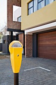 Bright yellow parking meter in front of house with garage and paved forecourt