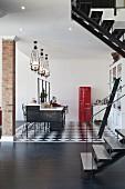 Offener Wohnraum mit Küchenblock unter Deckenleuchten in Gruppe und roter Fifty Kühlschrank auf schwarz weißem Boden, teilweise sichtbare Treppe im Vordergrund auf dunklem Holzboden