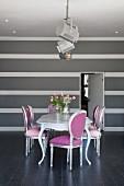 Neo Rokoko Stühle in Silber und Pink um Esstisch, dahinter grauweiss gestreifte Wand in elegantem, minimalistischem Ambiente