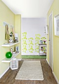 DIY renovations - hallway with floating shelves on yellow wall and pattern of green leaf stickers on grey wall