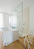 Light-flooded, designer bathroom with free-standing bathtub on parquet floor