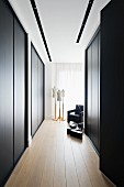 Elegant dressing area with floor-to-ceiling, black fitted wardrobes; tailors' dummies and black armchair in background