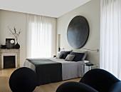 Elegantes Schlafzimmer mit französischem Bett, grauer Bettwäsche und rundem Kunstobjekt am Kopfende