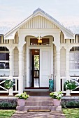 Traditional white wooden house - veranda with turned columns and plant pots on steps leading to half-open front door