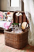 Open picnic basket with crystal carafes and orchid in metal pot; colourful scatter cushions on sofa in background