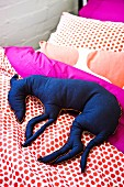 Blue fabric dog on polka-dotted bed linen