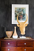 Clay pots and animal head sculpture on chest of drawers below small painting on dark wall