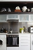 White fitted kitchen with wall units and various glass vessels and collectors' items on dark wooden shelf