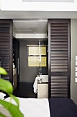 Elegant, masculine ensuite bathroom with dark brown, sliding louver doors