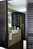 Masculine ensuite bathroom behind open, dark brown, sliding louver doors with elegant washstand and black fitted cupboard