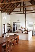 Esstafel mit verschiedenen antiken Stühlen aus Holz vor gemauerter Küchentheke in offener Küche, sichtbarer Dachstuhl aus Holz