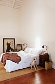Corner of minimalist bedroom - dog sitting on sisal rug in front of double bed with white bed linen, retro table lamp on bedside table, picture on floor leaning against wall