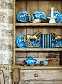 Small, brass horses in front of blue and white plates on shelves of rustic wooden dresser