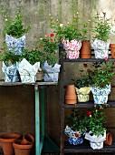 Blumentöpfe dekorativ umwickelt mit gemusterten Stoffen