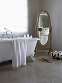 Old-fashioned free-standing mirror and claw foot bathtub standing on polished concrete floor