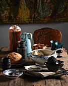 Eclectic collection of soup tureens, bowls, glasses and vases on rustic wooden table