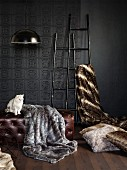 Furs draped over leather ottoman and ladders against embossed, anthracite wall