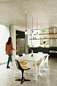 Dining table in open-plan house with exposed concrete surfaces; woman walking through room