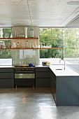 Anthracite, purist kitchen counter below suspended shelves in front of glass facade
