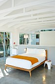 Bedroom with ensuite bathroom below exposed roof structure in glass-walled building