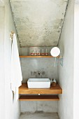 Narrow niche with washstand in house with exposed concrete walls