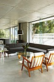 Corner sofa and retro armchairs in open-plan interior of contemporary concrete house