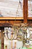 An Antique Candle Chandelier Hanging in a Greenhouse