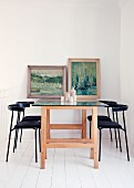 Black chairs, dining table made from wooden trestles and glass top & old paintings decorating wall