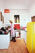Kitchen with white furnishings & yellow fridge providing a splash of colour