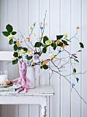 Selbstgehäkelter Osterhase vor Strauss aus Zweigen mit bunten Papierblüten dekoriert