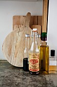 Vintage, swing-top bottle and bottles of vinegar and oil in front of wooden chopping boards