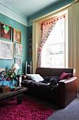 Ledersofa mit schlafendem Hund vor hohem Altbaufenster im Vintagelook, Bildergalerie an türkisfarbener Wand